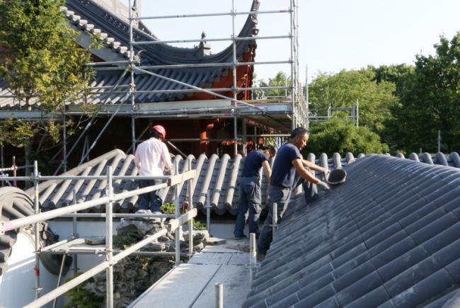 Réfection du Jardin de Chine - Été 2016 - Pose des tuiles sur les toits par les travailleurs chinois. Travaux de peinture.