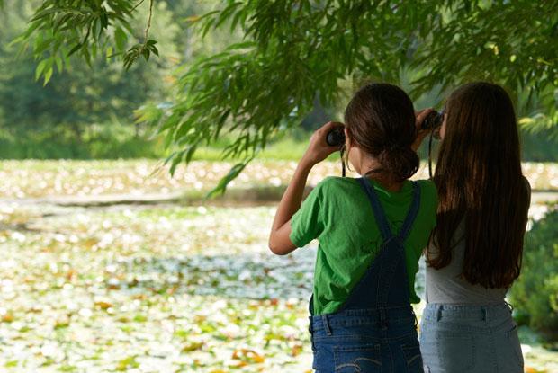 Two girls look at nature through binoculars at the Jardin Botanique de Montréal